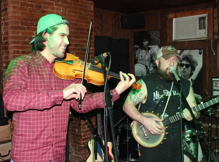 Nashwan Abdullah (left) plays his violin at a live show. Abdullah is unsure of his future after the executive order.