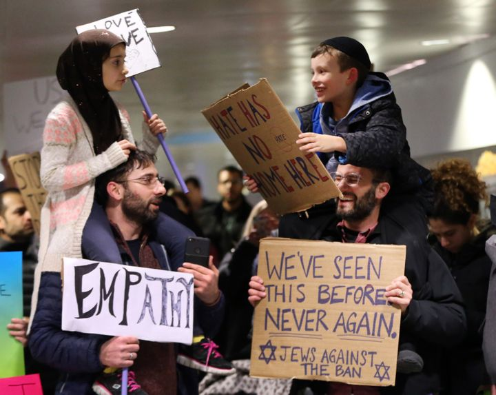 Chicago Tribune photographer Nuccio DiNuzzo captured a powerful moment between two fathers and their children at a protest at O'Hare International Airport.