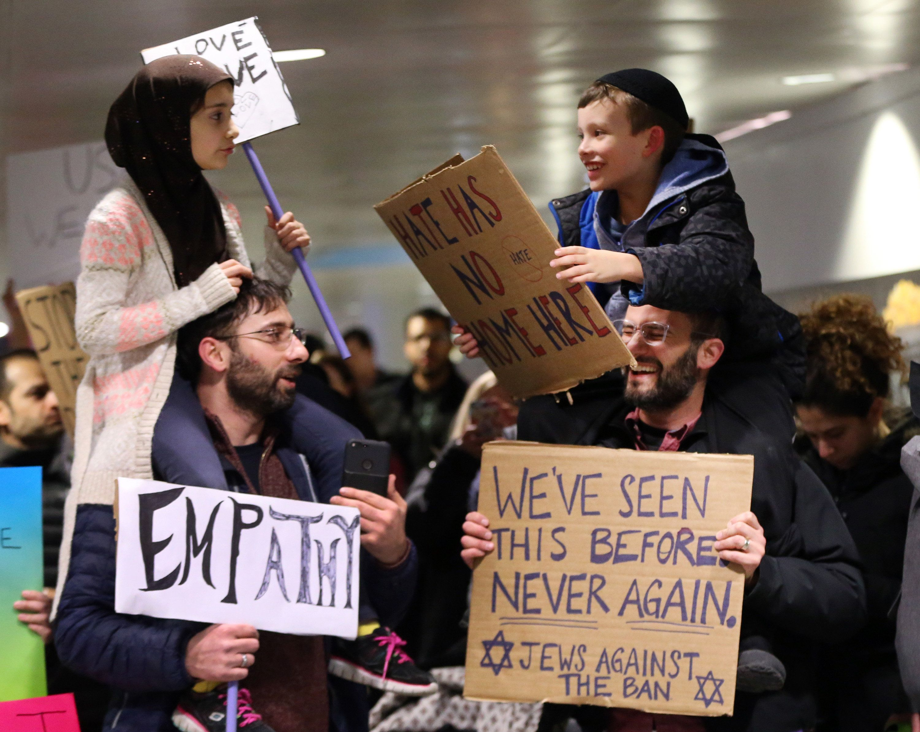 Meryem Yildirim, 7, left, sits on her father, Fatim, of Schaumburg, and Adin Bendat-Appell, 9, right, sits on his father, Rabbi Jordan Bendat-Appell, of Deerfield, during a protest on Monday, Jan. 30, 2017 at O'Hare International Airport in Chicago, Ill. (Nuccio DiNuzzo/Chicago Tribune/TNS via Getty Images)