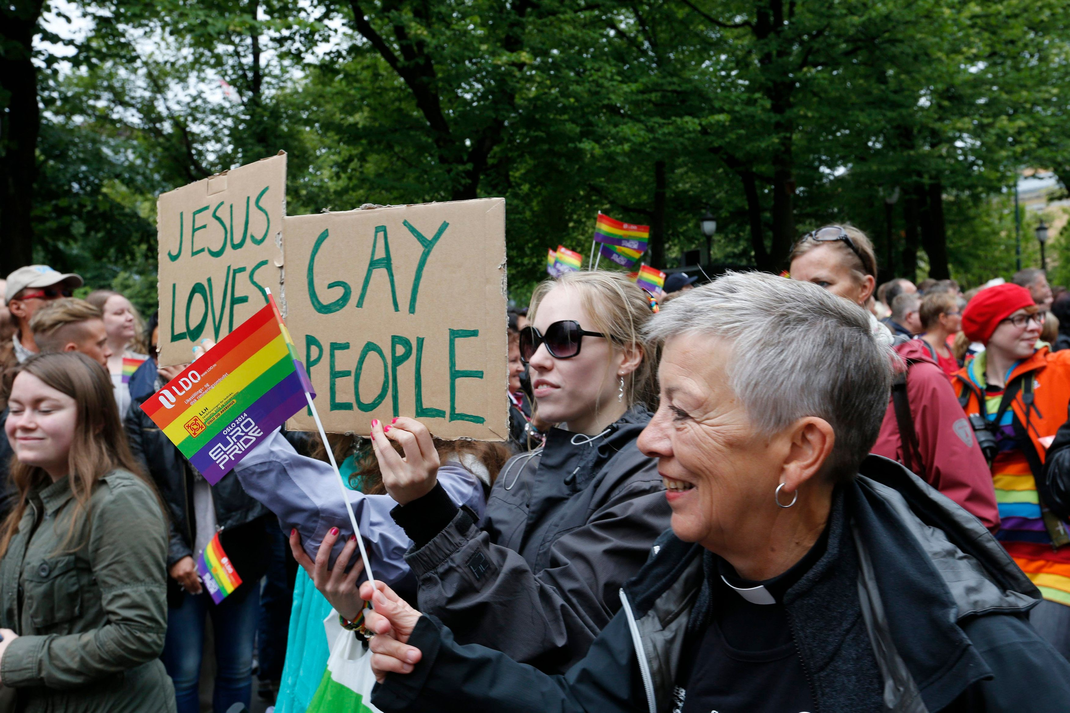 People hold a rainbow flag and signs during the EuroPride gay parade in downtown Oslo June 28, 2014. REUTERS/Terje Bendiksby/NTB Scanpix (NORWAY - Tags: SOCIETY)   ATTENTION EDITORS - THIS PICTURE WAS PROVIDED BY A THIRD PARTY. FOR EDITORIAL USE ONLY. NOT FOR SALE FOR MARKETING OR ADVERTISING CAMPAIGNS. THIS PICTURE IS DISTRIBUTED EXACTLY AS RECEIVED BY REUTERS, AS A SERVICE TO CLIENTS. NORWAY OUT. NO COMMERCIAL OR EDITORIAL SALES IN NORWAY. NO COMMERCIAL SALES