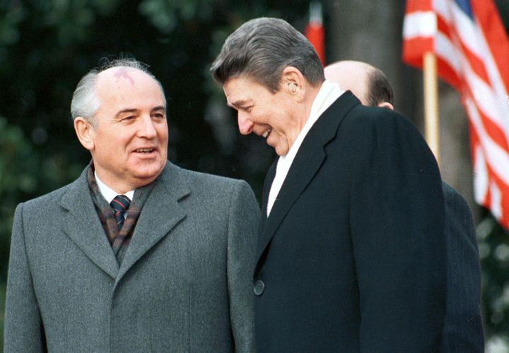 Former U.S. President Ronald Reagan stands with former Soviet leader Mikhail Gorbachev during Gorbachev's arrival ceremony at