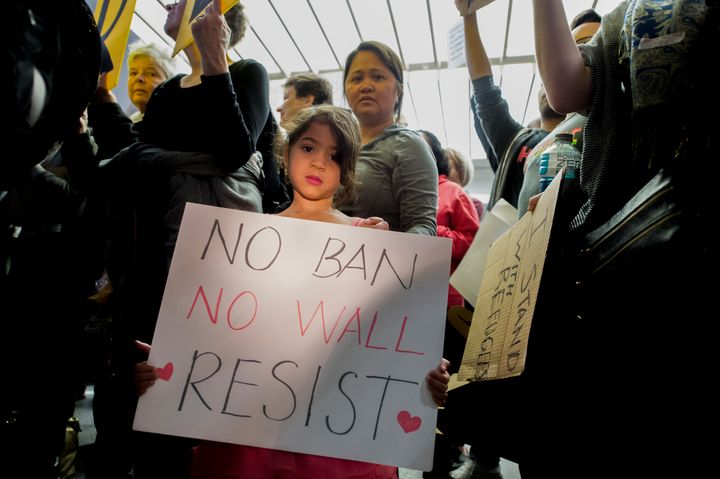 A young girl holding a sign during a protest at San Francisco airport.