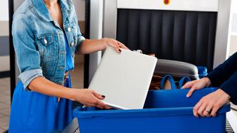 Close up of woman's hands putting a laptop into a container at airport security checkpoint.