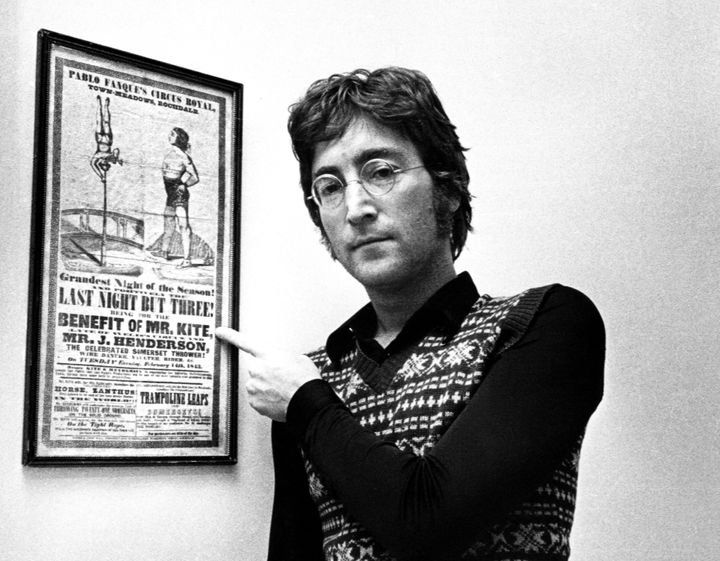 John Lennon posing with the Victorian circus poster