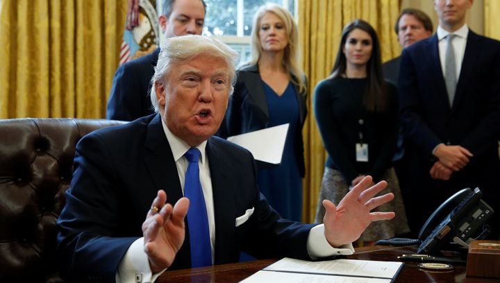 U.S. President Donald Trump speaks to reporters while signing executive orders at the White House in Washington January 24, 2