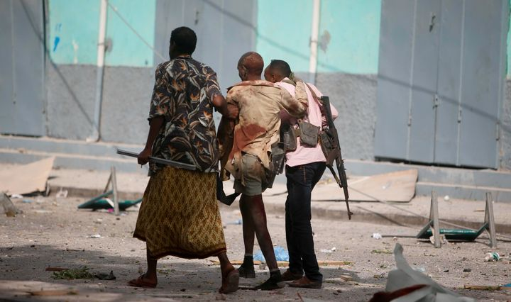 A injured government soldier is led away from the scene of an explosion in Somalia's capital, Mogadishu, on Jan. 25. Civ