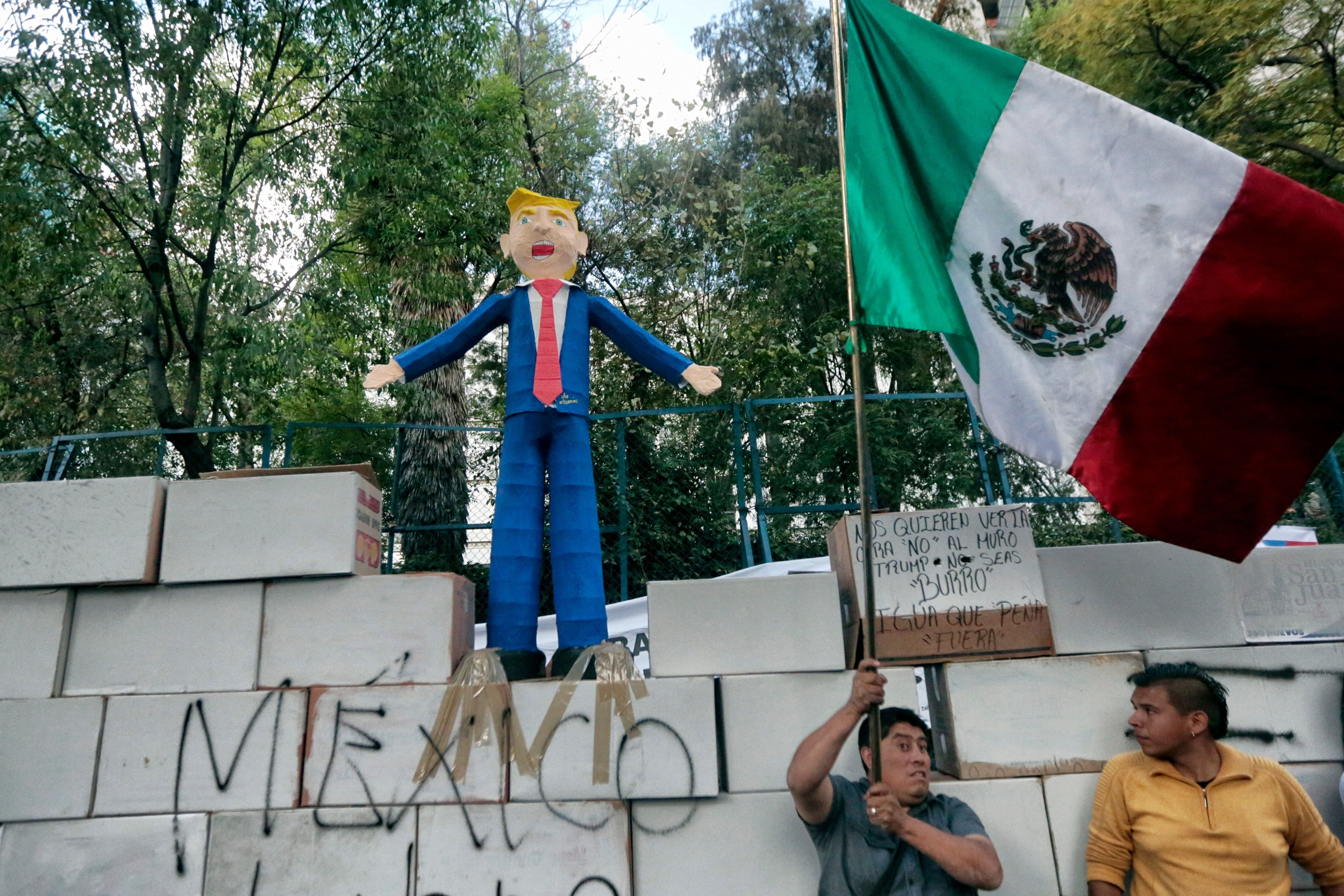 People protest against US President Donald Trump's inauguration next to a fake wall with a Mexican national flag and a dummy representing him in Mexico City on January 20, 2017. Billionaire outsider Donald Trump was sworn in on Friday as the 45th president of the United States and announced that he will shield the country's borders against immigrants and protect it from the 'ravages' of free trade. / AFP / PEDRO PARDO        (Photo credit should read PEDRO PARDO/AFP/Getty Images)