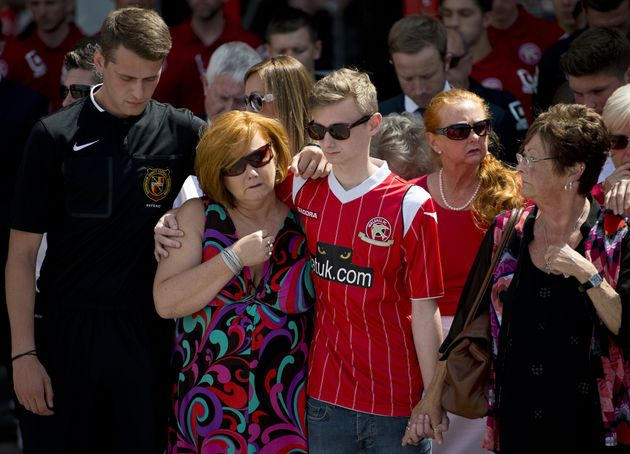 Owen and his mother Suzanne observing a minute's silence at Walsall football club for his brother, uncle...