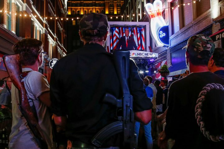 Kevin Kvasnicka and Jesse Gonzales openly carry firearms as they watch Donald Trump speak during the Republican National Conv