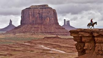 A Navajo man on a horse poses for tourists in front of the Merrick Butte in Monument Valley Navajo Tribal Park, Utah, on May 16, 2015. AFP PHOTO/MLADEN ANTONOV        (Photo credit should read MLADEN ANTONOV/AFP/Getty Images)