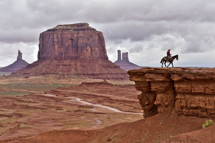 A Navajo man on a horse poses for tourists in front of Merrick Butte in Monument Valley Navajo Tribal Park, Utah, on May 16,