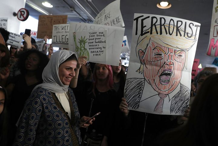 International travelers are welcomed by protesters during a demonstration against the immigration ban imposed by U.S. Pr