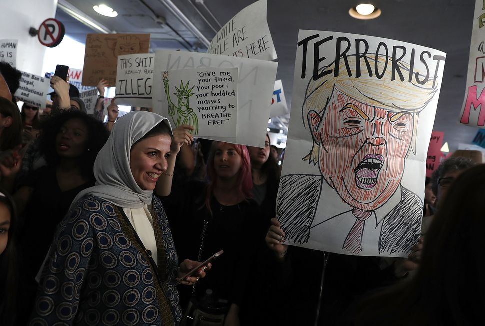 International travelers are welcomed by protesters holding signs during a demonstration against the immigration ban that was