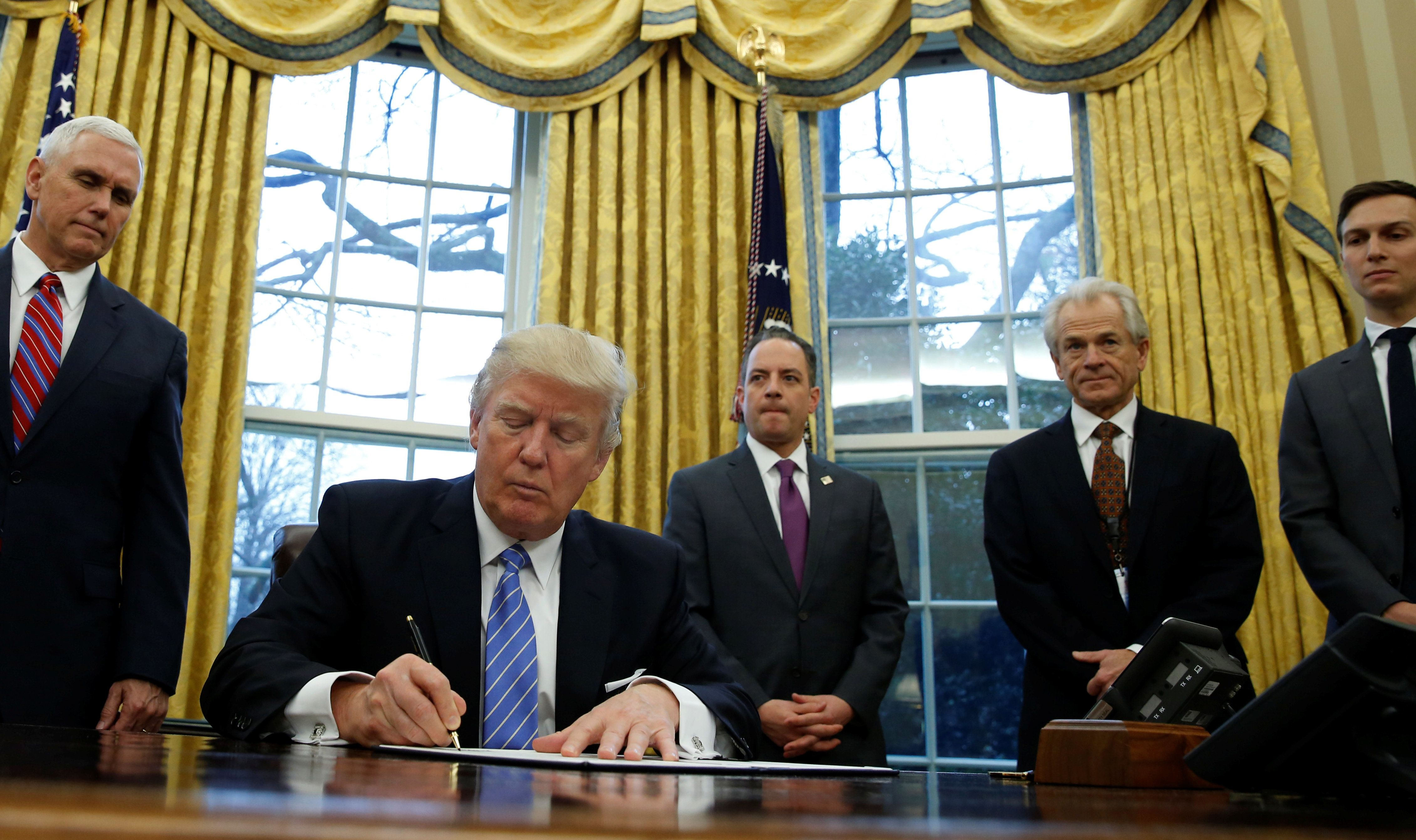 President Donald Trump signs an executive order that places a hiring freeze on non-military federal workers, Jan. 23, 2017.