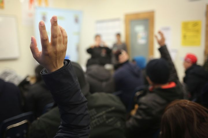 People raise their hands as Immigrants attend a workshop for Deferred Action for Childhood Arrivals (DACA), on February 18, 2