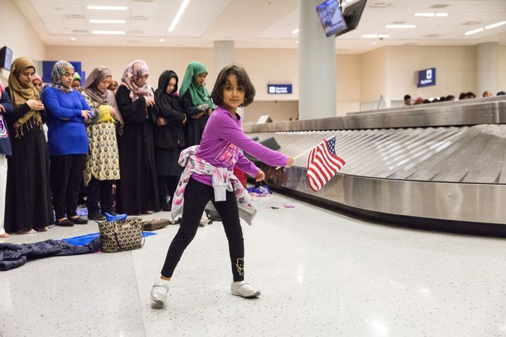 A young girl dances with an American flag in baggage claim at Dallas/Fort Worth International Airport on Jan. 29 while women