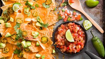 An overhead close up shot of an old metal tray with some nachos and a container of salsa.