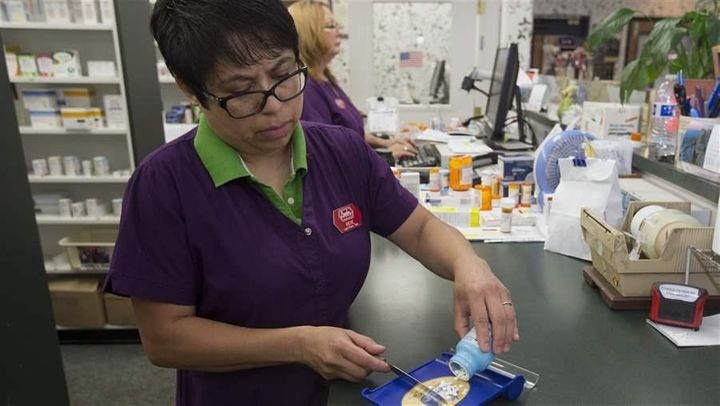 A pharmacist fills a prescription in Sacramento. California has limited insurers' ability to make midyear changes to covered