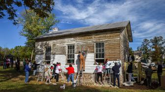 ASHBURN, VA - OCTOBER 9: A group tackles painting the exterior as volunteers gather to restore the Ashburn Colored School, a nineteenth-century schoolhouse recently vandalized with racist symbols and hate language, on October, 09, 2016 in Ashburn, VA.   (Photo by Bill O'Leary/The Washington Post via Getty Images)