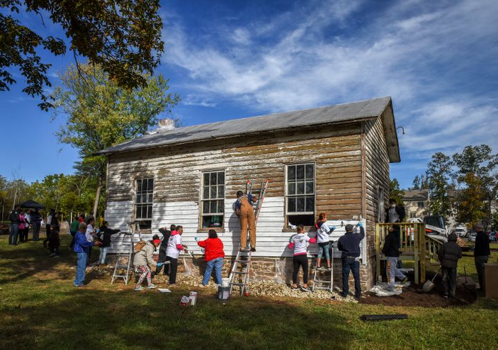 A volunteer group painting the exterior of the Ashburn Colored School, a nineteenth-century schoolhouse recently vandalized w