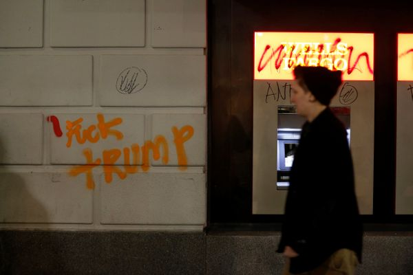 A pedestrian walks by a vandalized Wells Fargo bank office.
