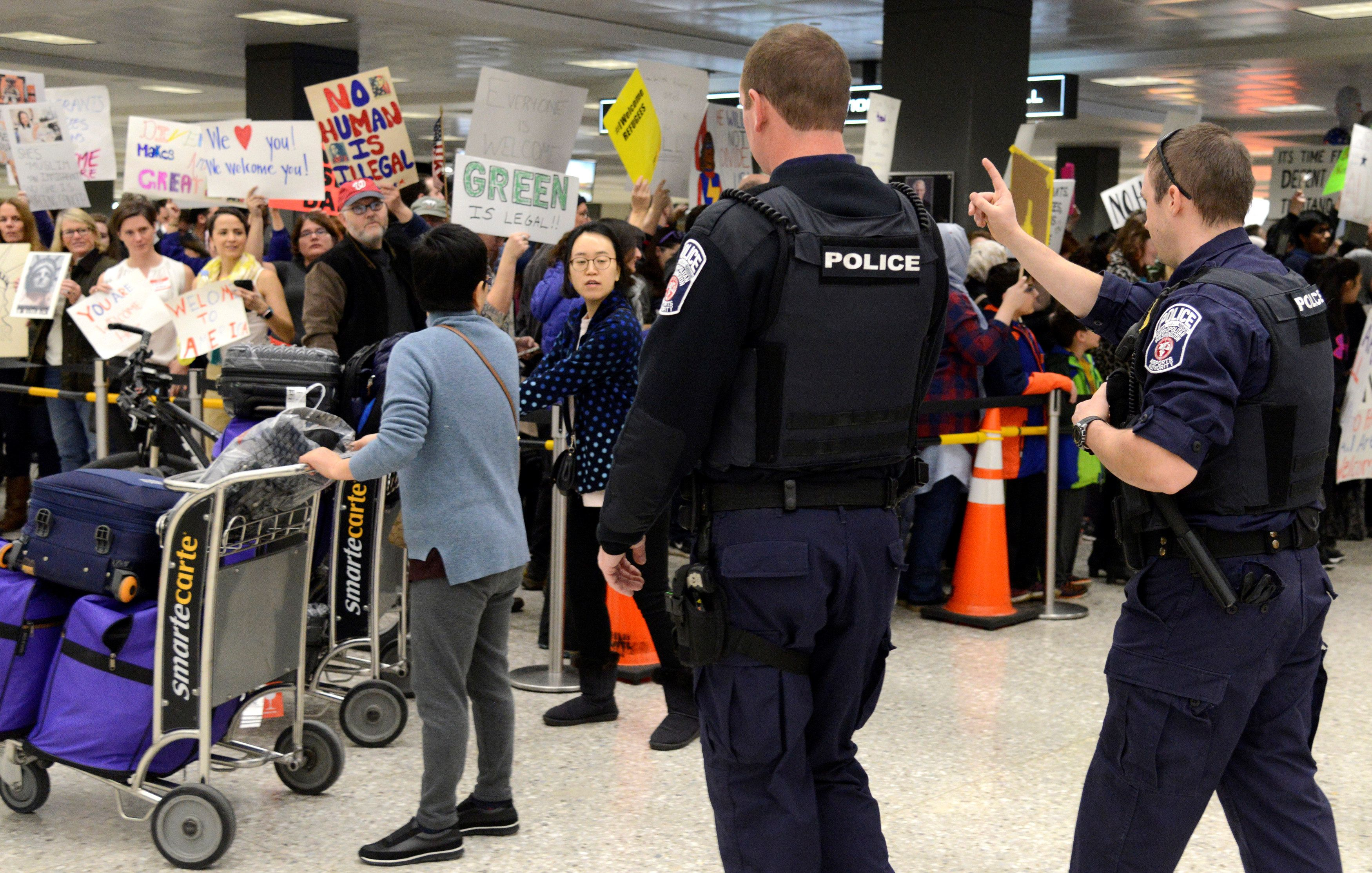 Police direct arriving passengers past dozens of pro-immigration demonstrators who cheer and hold signs at Dulles International Airport, to protest President Donald Trump's travel ban in Chantilly, Virginia, in suburban Washington, U.S., January 29, 2017.  REUTERS/Mike Theiler