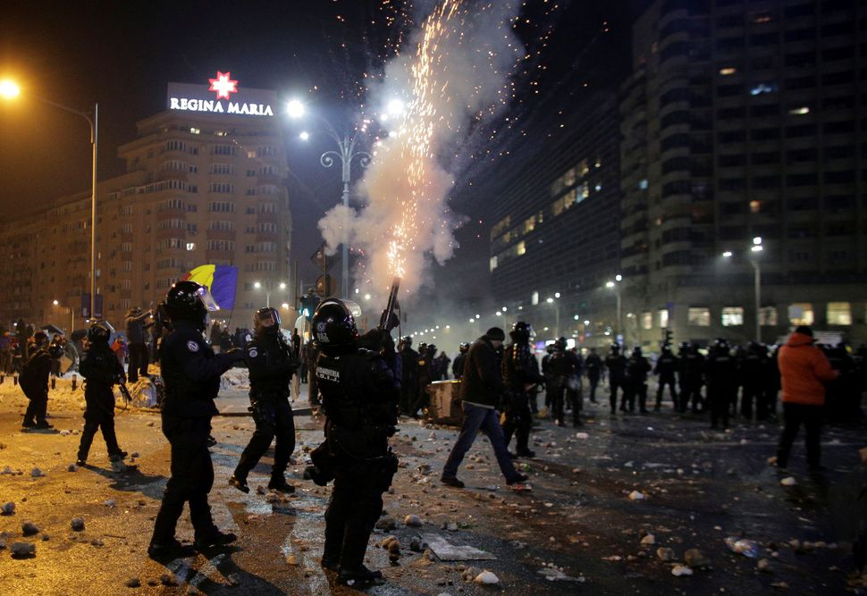 A Romanian police officer fires in the air at a demonstration in Bucharest, Romania, on Feb. 1, 2017.