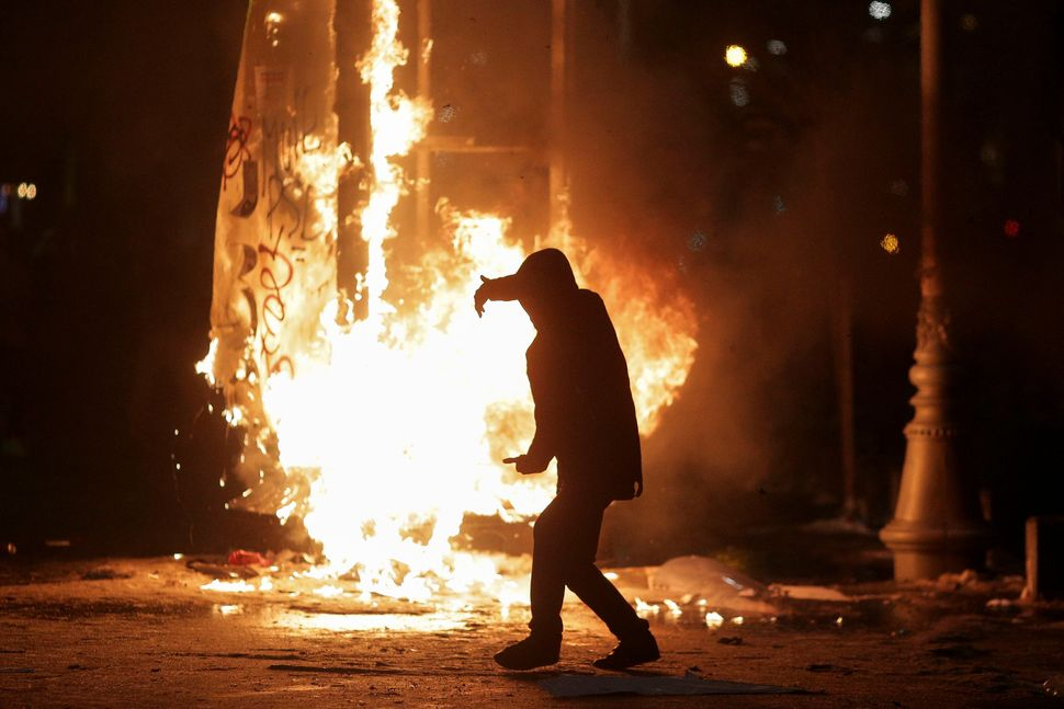 A protester walks in front of a burning street sign in Bucharest, Romania, on Feb. 1, 2017.