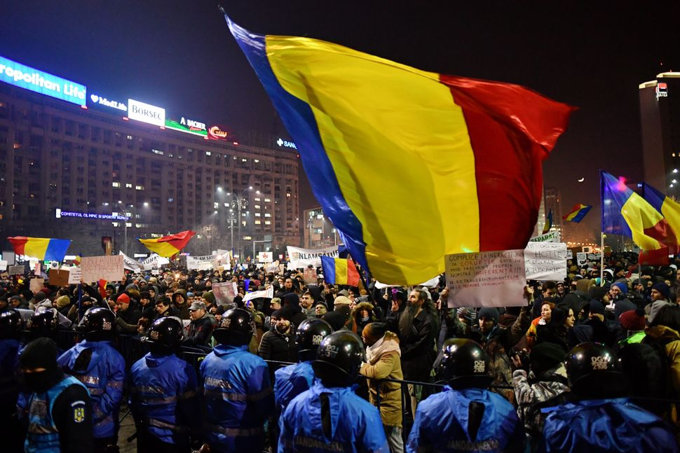 Romanian riot police stand guard as people demonstrate against decriminalizing corruption in Bucharest, Romania, on Feb. 1, 2