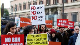 Demonstrators hold placards during a protest against U.S. President Donald Trump's executive order travel ban outside U.S. Embassy in Rome, Italy February 2, 2017. REUTERS/Tony Gentile