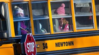 Children from Sandy Hook Elementary School are seen on a school bus making their way to their new school in Monroe as they leave Newtown, Connecticut January 3, 2013. Hundreds of the children who escaped the harrowing attack on their elementary school in Newtown, Connecticut, last month head back to classes on Thursday for the first time since a gunman killed 20 of their schoolmates and six staff members. School officials are preparing for droves of anxious parents to join the fleet of buses carting children to a disused middle school in the neighboring town of Monroe. REUTERS/Shannon Stapleton (UNITED STATES - Tags: CRIME LAW EDUCATION)