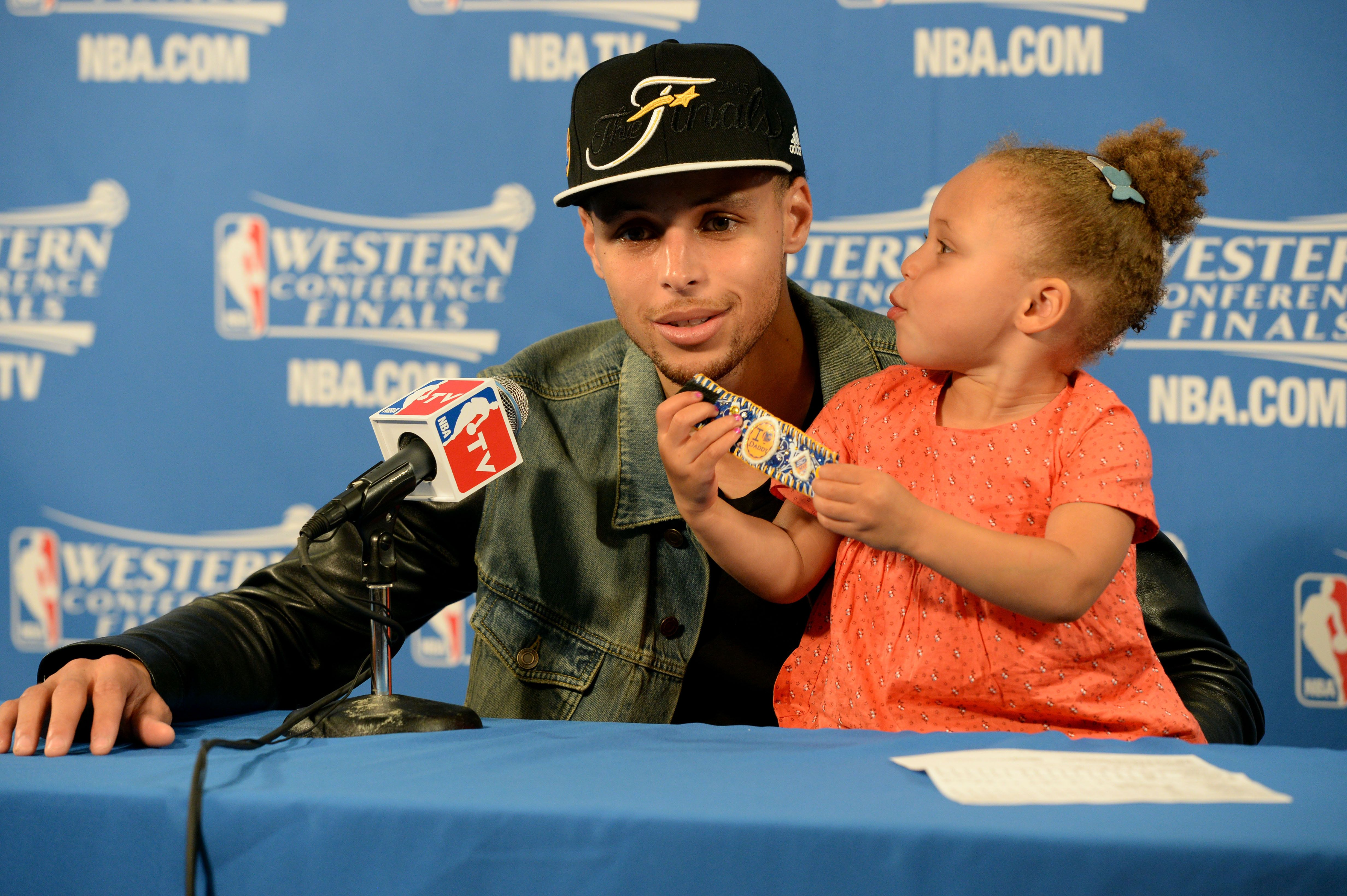 OAKLAND, CA - MAY 27: Stephen Curry #30 of the Golden State Warriors speaks to the media with daughter Riley Curry after a game against the Houston Rockets in Game Five of the Western Conference Finals during the 2015 NBA Playoffs on May 27, 2015 at ORACLE Arena in Oakland, California. NOTE TO USER: User expressly acknowledges and agrees that, by downloading and or using this Photograph, user is consenting to the terms and conditions of the Getty Images License Agreement. Mandatory Copyright Notice: Copyright 2015 NBAE (Photo by Andrew D. Bernstein/NBAE via Getty Images)