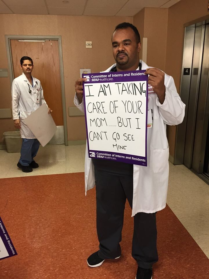 Dr. Mazin Khalid went to medical school with Dr. Kamal Fadlalla and is his friend. He's holding a sign writtenby anothe