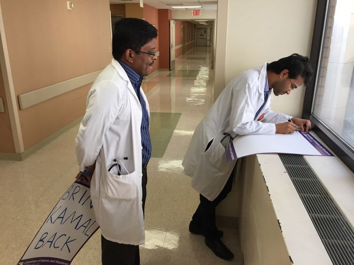 Dr. Sumit Dahal writes his message on the sign Khalid held for him in the viral photo.
