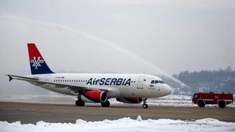 A firefighting vehicle sprays water near an Air Serbia Airbus A319 aircraft at Banja Luka International Airport during a ceremonial welcome in Banja Luka, December 1, 2013.  Air Serbia begins its first direct flight between Belgrade and Banja Luka on Sunday. REUTERS/Dado Ruvic (BOSNIA AND HERZEGOVINA - Tags: TRANSPORT BUSINESS)