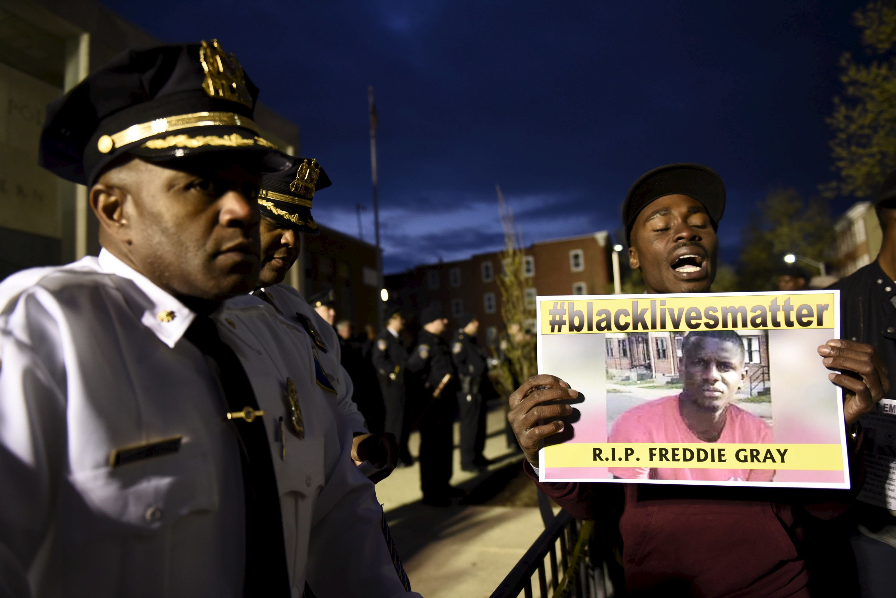 A demonstrator holds a sign in front of the Baltimore Police Department Western District station during a protest against the death in police custody of Freddie Gray in Baltimore April 23, 2015. The U.S. Southern Christian Leadership Conference will independently investigate the death of a black Baltimore man in police custody, with the local head of the civil rights group saying it lacked confidence in a police probe into the death. REUTERS/Sait Serkan Gurbuz