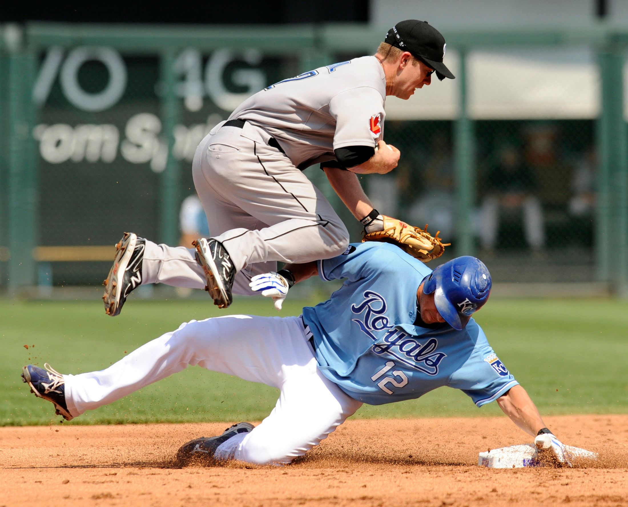 Toronto Blue Jays second baseman Aaron Hill hurdles Kansas City Royals Mitch Maier after Meier broke up the double play in th