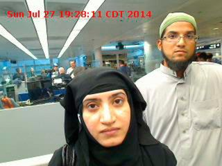Tashfeen Malik, left, and Syed Farook are pictured passing through Chicago's O'Hare International Airport in this July 27, 20