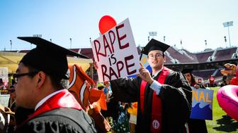 Stanford student Paul Harrison (C) carries a sign in a show of solidarity for a Stanford rape victim during graduation ceremonies at Stanford University, in Palo Alto, California, on June 12, 2016.  Stanford students are protesting the universitys handling of rape cases alledging that the campus keeps secret the names of students found to be responsible for sexual assault and misconduct. / AFP / GABRIELLE LURIE        (Photo credit should read GABRIELLE LURIE/AFP/Getty Images)