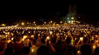 Members of the community hold up candles as they listen to taps being played during a commemoration and candlelight vigil on the campus of Virginia Tech in Blacksburg, Virginia April 16, 2012. Five years after a mentally ill student gunned down 32 people at Virginia Tech, the university on Monday held classes for the first time on the anniversary of the country's deadliest mass shooting. REUTERS/Chris Keane (UNITED STATES - Tags: CRIME LAW ANNIVERSARY)