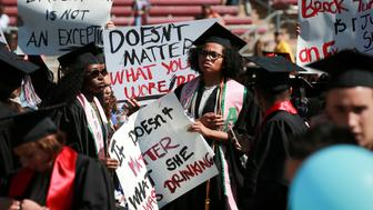 Protesters hold signs to raise awareness of sexual assault on campus in the wake of the national attention brought by the Stanford rape case at the Stanford University commencement ceremony in Palo Alto, California, U.S. June 12, 2016. The case made national headlines after the judge handed down what many considered to be a particularly light sentence. REUTERS/Elijah Nouvelage