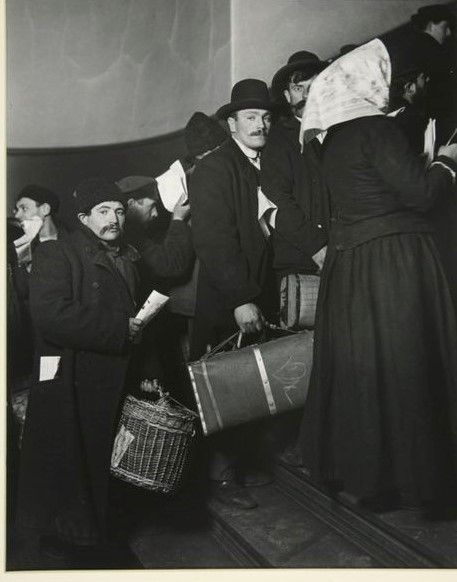<strong>Climbing into America, Ellis Island, 1908. </strong>The man wearing a homburg and carrying a suitcase was among the m