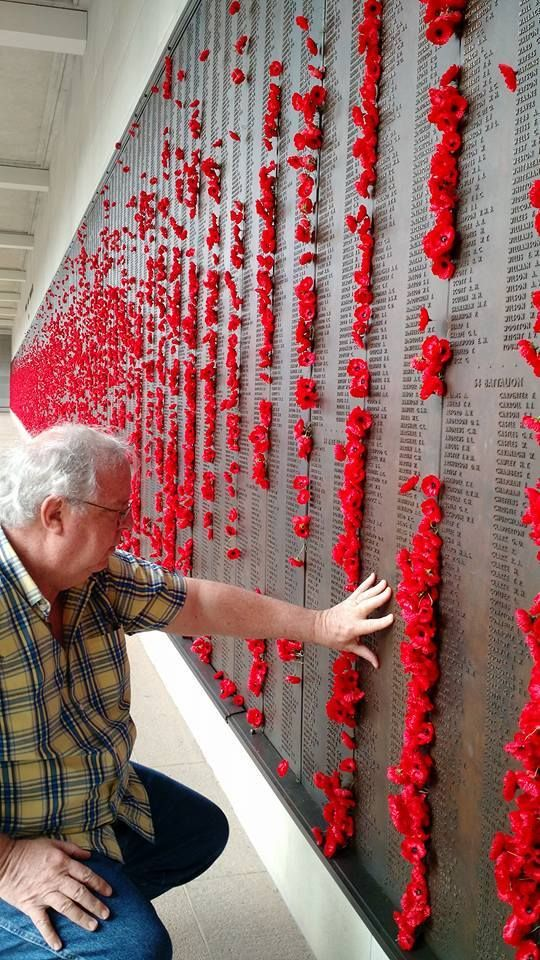The author touches one of the bronze and engraved walls at the Australian War Memorial in Canberra, honoring more than 102,00