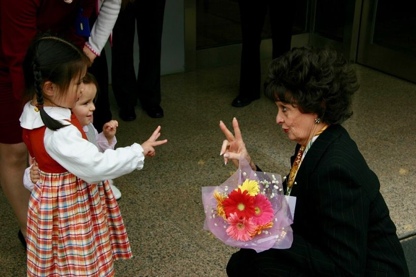 Marilyn Carlson Nelson is greeted by children in Asia.