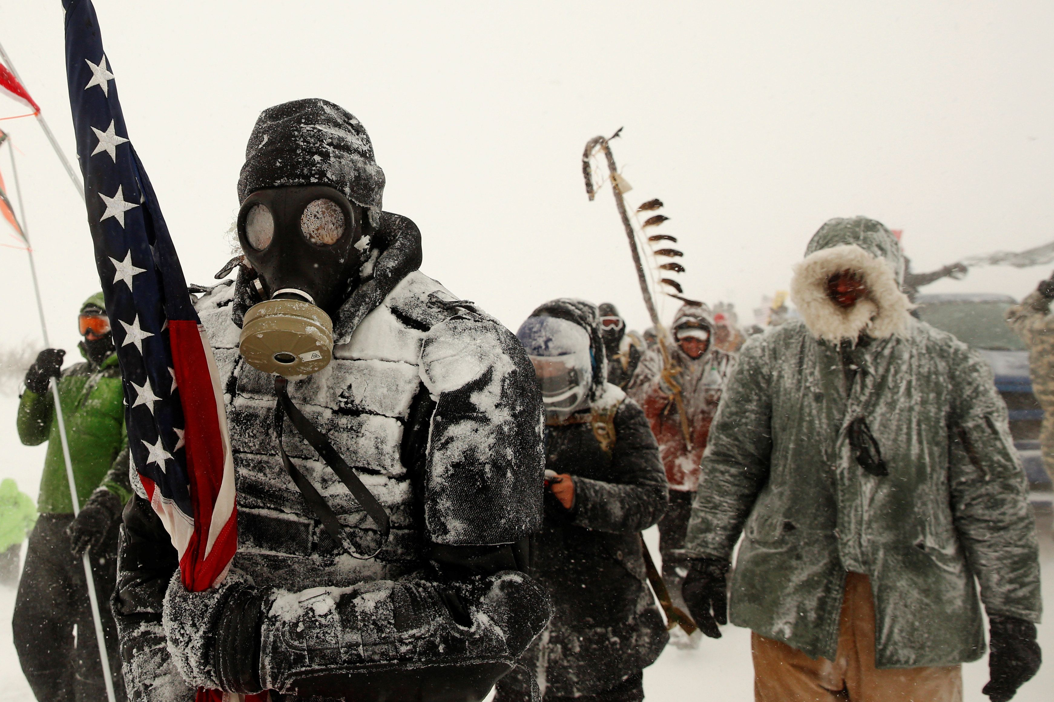 """A man takes part in a march with veterans to Backwater Bridge just outside of the Oceti Sakowin camp during a snow fall as """"water protectors"""" continue to demonstrate against plans to pass the Dakota Access pipeline adjacent to the Standing Rock Indian Reservation, near Cannon Ball, North Dakota, U.S., December 5, 2016.  REUTERS/Lucas Jackson"""