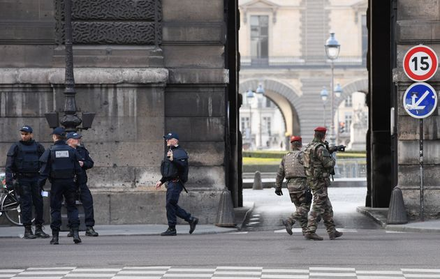 French police officers and soldiers patrol in front of the Louvre