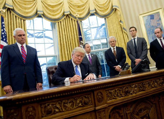 This photo of Donald Trump signing an executive order to limit abortion rights access flanked by a group...