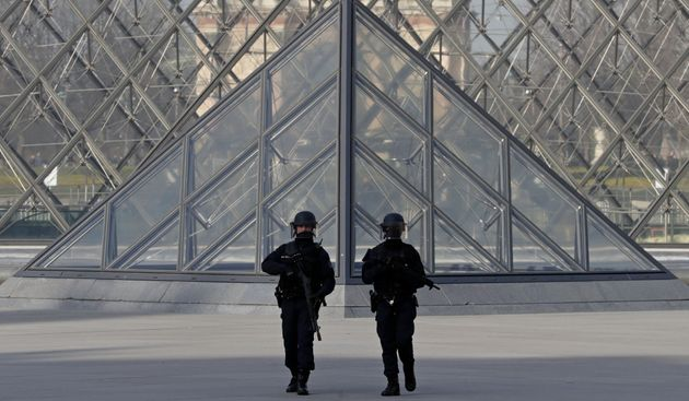 French police secure the site near the Louvre Pyramid in Paris, France following Friday's terror