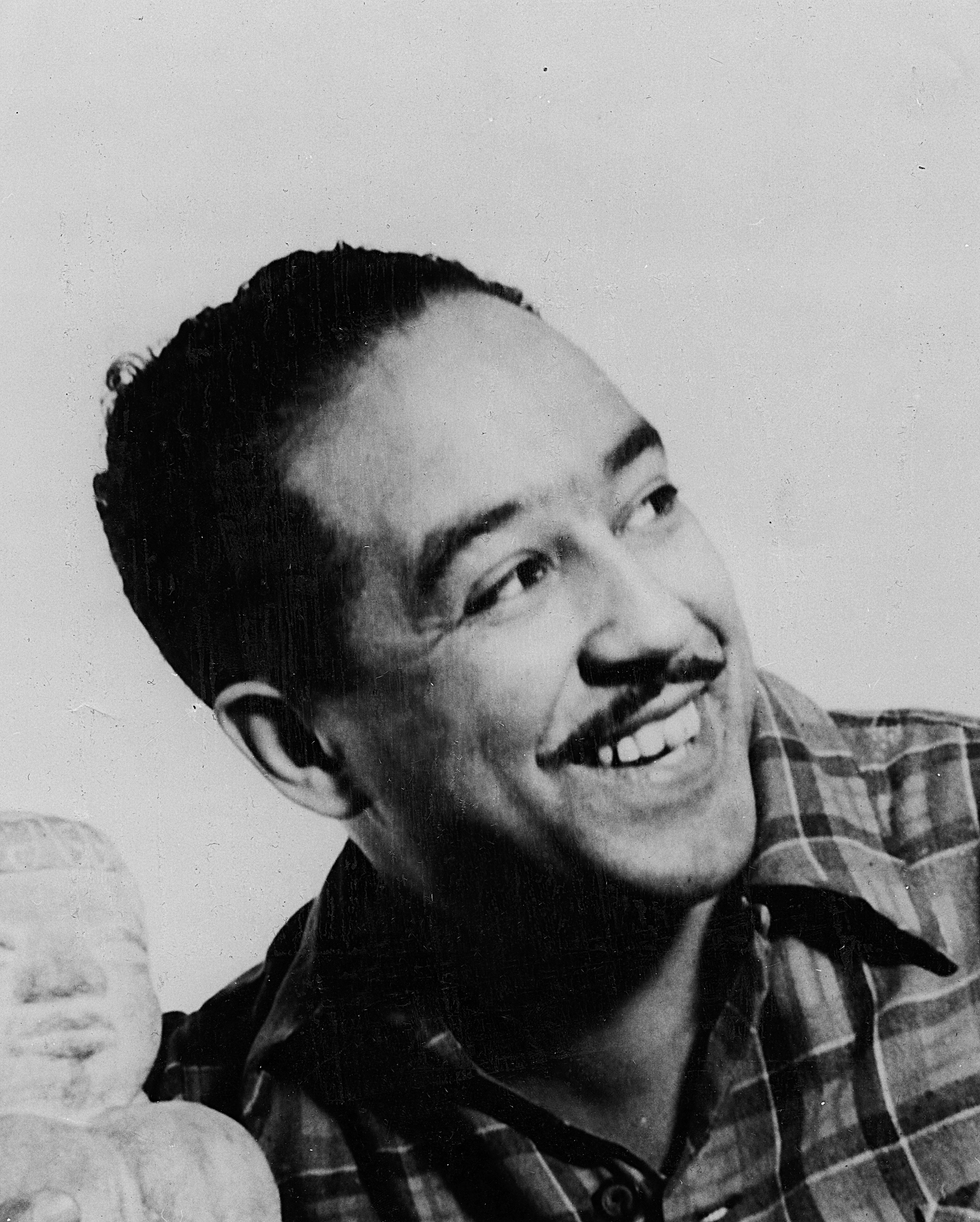 Portait of African American poet Langston Hughes with a statue, 1955. (Photo by Afro American Newspapers/Gado/Getty Images)