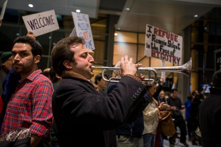 "A protester plays ""This Land Is Your Land"" on a trumpet during a demonstration against the ban on immigration issued by Presi"